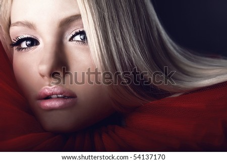 Attractive blond beauty in a red theatrical jabot. Close-up Portrait.