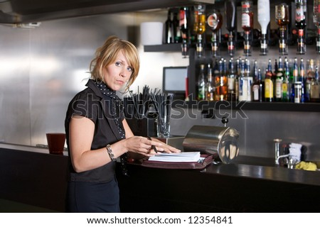 Attractive blond business woman standing in a bar with her notebook