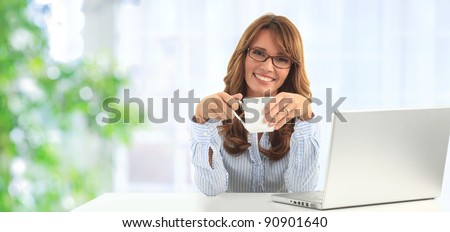 Attractive blond business woman working on her laptop and drinking coffee in her office (blue background) - stock photo