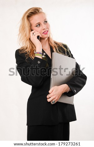 Attractive blond caucasian businesswoman carrying laptop - stock photo