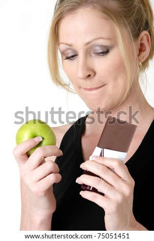 Attractive blond caucasian woman holding an apple and chocolate bar trying to decide which one to eat while biting on her lip - stock photo