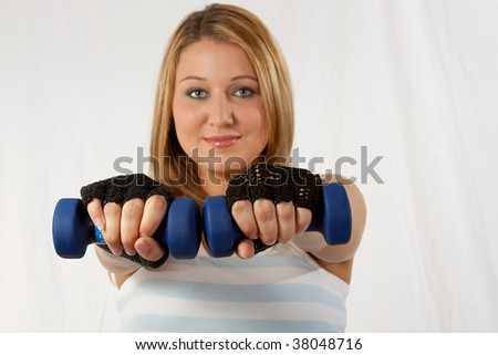 Attractive blond caucasian woman wearing workout attire with hands forward holding two three pound blue weights focus on hands - stock photo