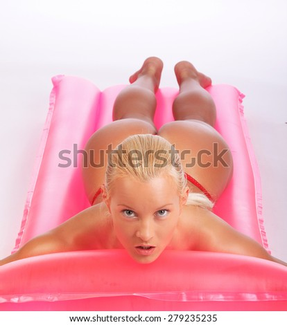 Attractive blond female lying on pink water matress. Isolated on white background - stock photo