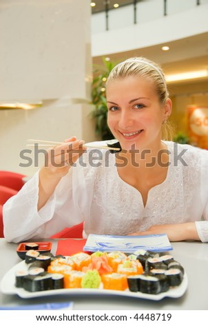 Attractive blond girl eats sushi in a restaurant