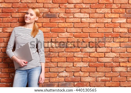 Attractive blond girl holding modern computer - stock photo