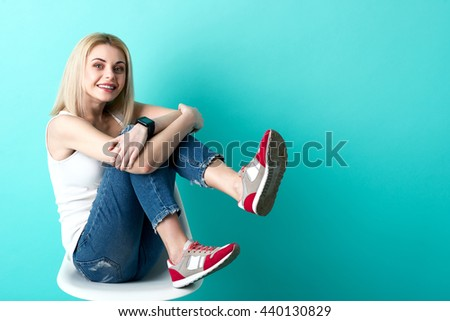 Attractive blond girl is relaxing on chair - stock photo