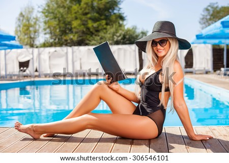 Attractive blond girl is sitting and relaxing near a swimming pool. She is holding a magazine and smiling. The lady is looking at the camera with happiness - stock photo
