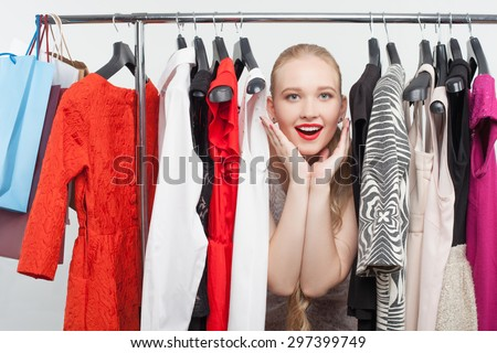Attractive blond girl is standing between dresses hanging on rack. She is raising her hand to her cheek and smiling happily - stock photo