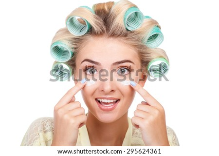 Attractive blond girl with curlers in hair is doing make-up. She is covering her face with cream. She is looking forward with surprise. Isolated on background - stock photo