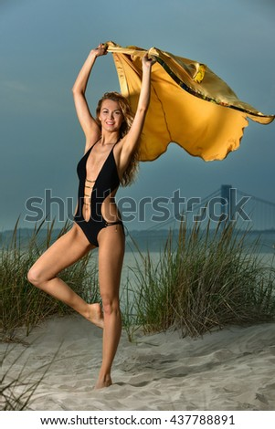 Attractive blond girl with slim fit body  posing on the beach wearing elegant black swimsuit and holding floating silk shirt. Sunset time. - stock photo
