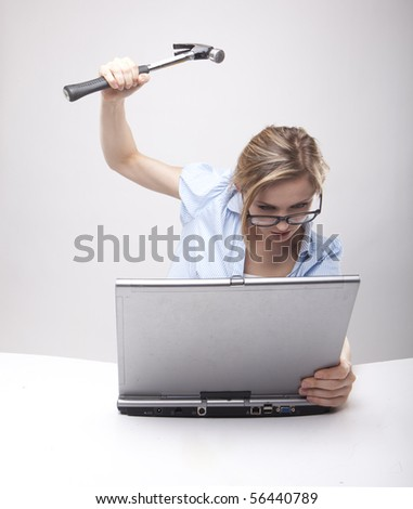 Attractive blond hair woman wearing business suit sitting in front of a computer with angry facial expression holding a hammer and wearing glasses - stock photo