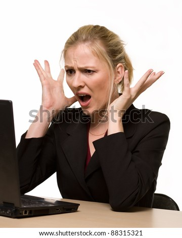 Attractive blond hair woman wearing business suit sitting in front of a computer with angry facial expression with hands up while looking at the computer as if it crashed or broke