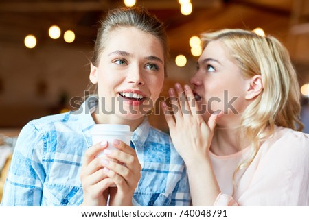 Attractive blond-haired woman sharing secret with friend while sitting at cozy small coffeehouse and enjoying cappuccino, blurred background