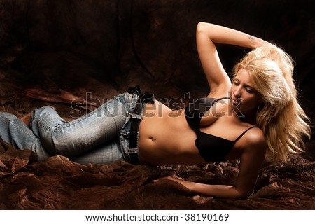 attractive blond in jeans and bra, studio shot - stock photo