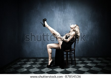 attractive blond in long black dress and ciggarette sit on chair indoor shot - stock photo