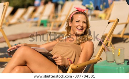 Attractive blond lying on a sunbed on a beach, reading a magazine and enjoying the sun - stock photo