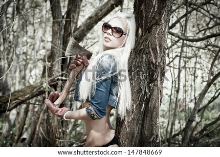 Attractive blond model with an axe in a forest - stock photo