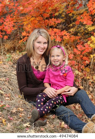 attractive blond mother holding daughter outdoor in fall - stock photo