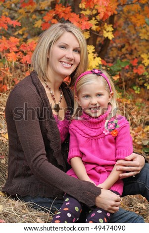 attractive blond mother holding happy daughter outdoor in fall - stock photo