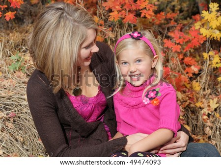 attractive blond mother holding smiling daughter outdoor in fall - stock photo