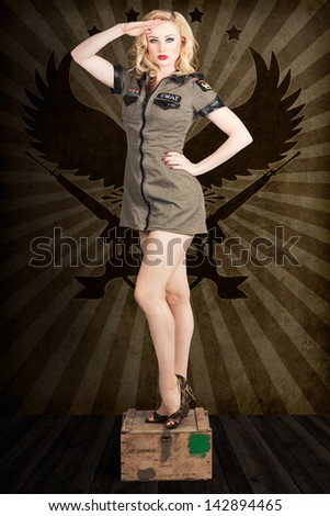Attractive blond pin-up army girl addressing a command with a general salute, standing on military ammunition box - stock photo
