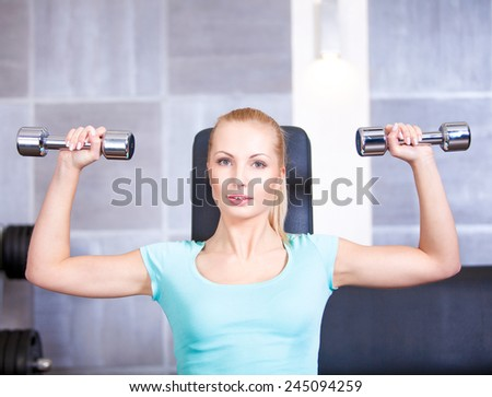 Attractive blond   sporty girl doing shoulders training with a dumbbell - stock photo