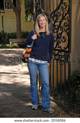Attractive blond student walking between classes - stock photo