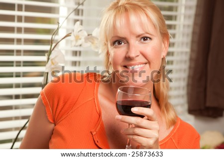 Attractive Blond with a Glass of Wine in the Kitchen - stock photo