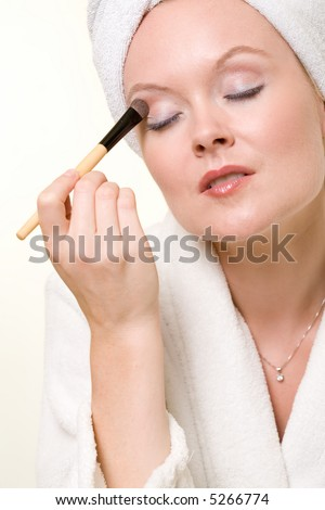 Attractive blond woman applying makeup wearing white robe and towel over hair