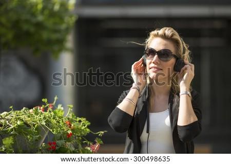 Attractive blond woman enjoying music in headphones outdoors. - stock photo