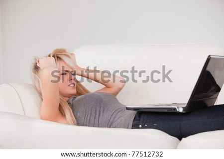 Attractive blond woman frustrated with her computer lying on a sofa in a studio - stock photo