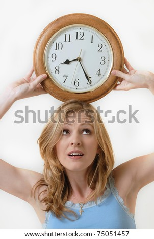 Attractive blond woman holding a round clock balanced on head at the time eight twenty-five showing time management