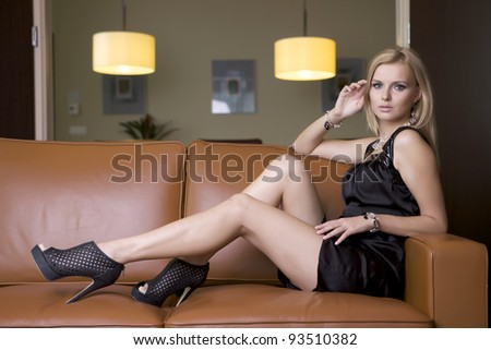 attractive blond woman in black dress sitting on the couch - stock photo