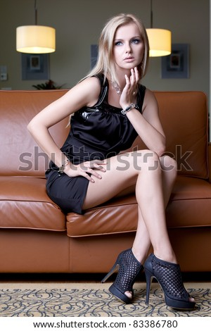 attractive blond woman in black dress sitting on the sofa