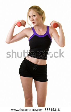 Attractive blond woman in black shorts and workout top doing arm exercises with two red three pound weights on white - stock photo