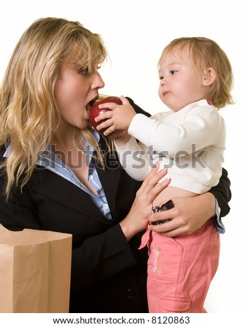 Attractive blond woman in business attire carrying a young baby girl while baby is feeding mom an apple - stock photo