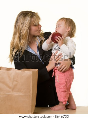 Attractive blond woman in business attire carrying a young baby girl while baby is holding a large apple - stock photo