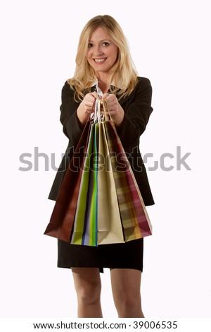 Attractive blond woman in business attire smiling and holding in front of her four shopping bags - stock photo