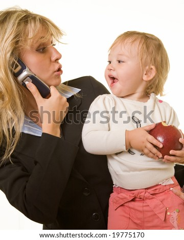 Attractive blond woman in business attire talking on cell phone carrying a cute baby girl with an apple looking at each other with cute expression - stock photo