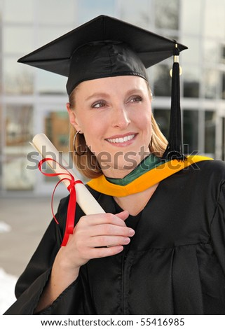 attractive blond woman in graduation cap and gown on campus holding diploma