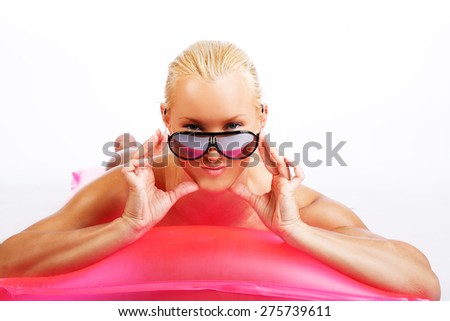 Attractive blond woman lying on a pink water matress. Isolated on white background - stock photo