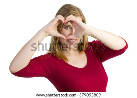 Attractive blond woman making a heart symbol with her hands and looking through it. - stock photo