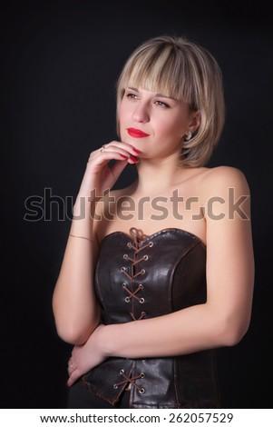 Attractive blond woman posing on studio dark background - stock photo