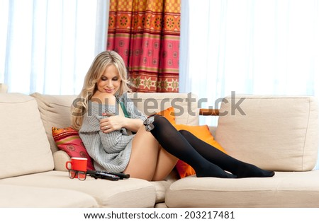 attractive blond woman relaxing on the sofa in her home - stock photo