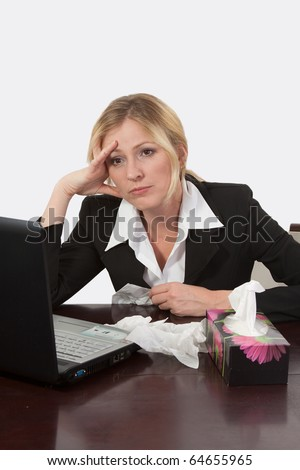 Attractive blond woman sitting at desk in front of computer with box of tissue tissues looking ill