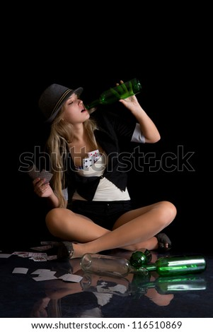 Attractive blond woman sitting on dirty floor holding empty bottle of wine and playing cards - stock photo
