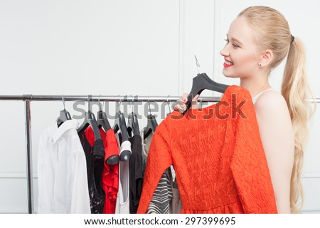 Attractive blond woman wants to try on a new red dress in boutique. She is holding it and smiling - stock photo