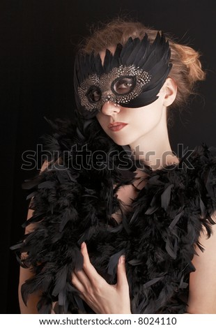 attractive blond woman wearing black carnival mask and feathers around her body, role play - stock photo