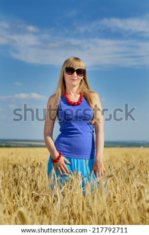 Attractive blond woman wearing sunglasses and a summer top standing enjoying the sun in a wheat field with her arms outstretched and head tilted to the sun with a smile - stock photo