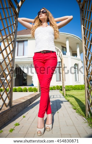 Attractive blond woman wearing white top and red panties posing in archway outdoors - stock photo